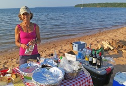 A woman standing behind a table of food on a beach.