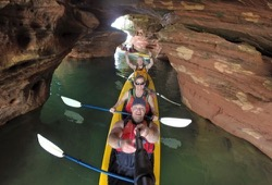 Three people in a yellow kayak paddling through a sea cave.
