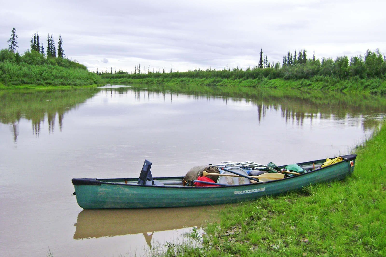 A single tandem canoe loaded up with gear sits on a grassy shore of the calm river.