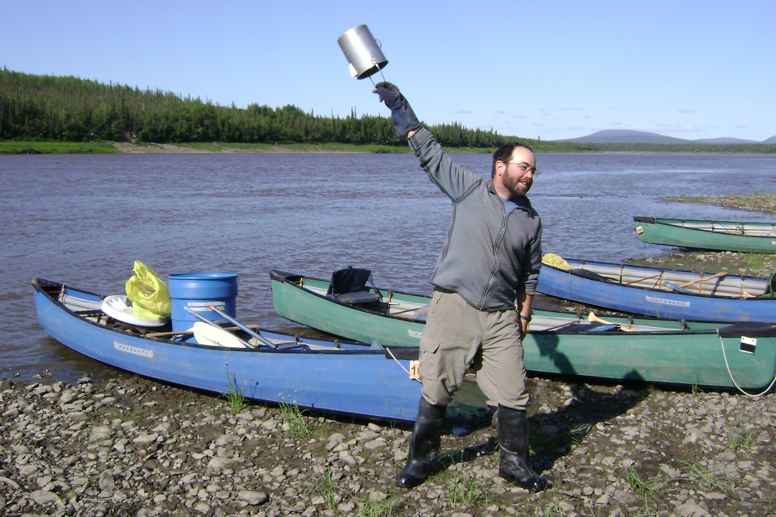 "A man swings a coffee pot to make ""cowboy coffee"" on the shores of the Porcupine River."