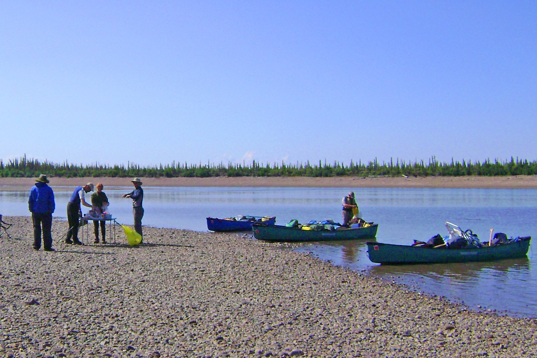 Participants stop for lunch on a rock beach along the Porcupine River; canoes sit in the water along the shore.