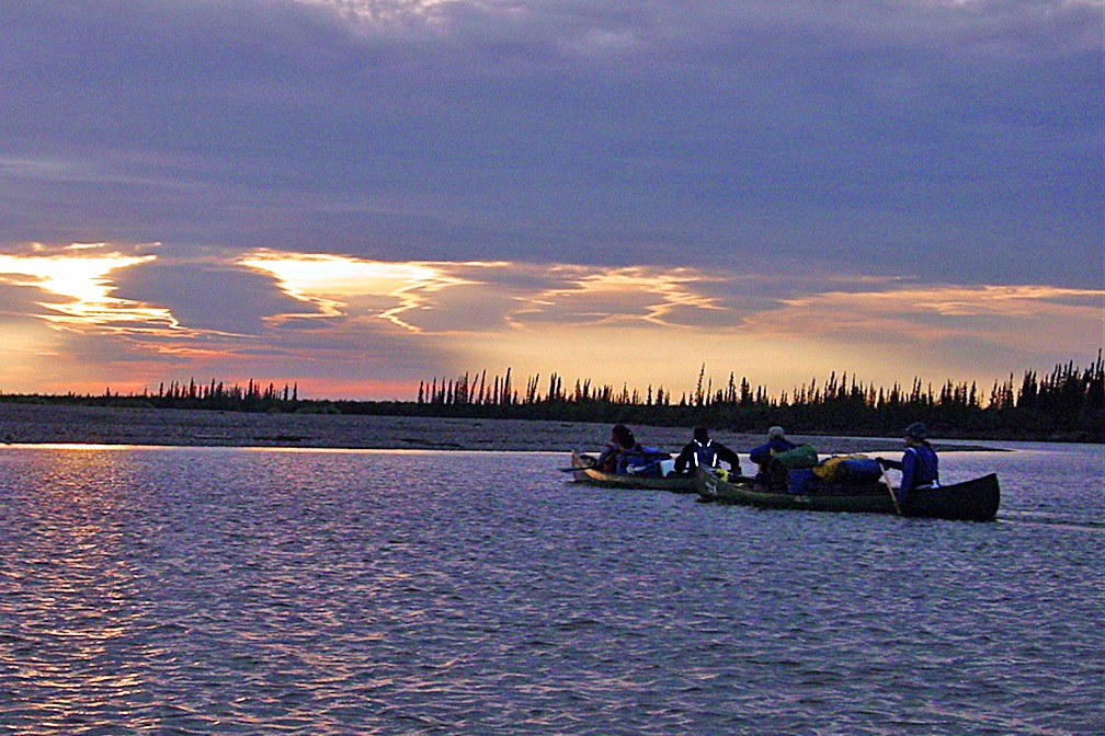 The sun breaks through the clouds over the waters as two tandem canoes paddle towards shore.
