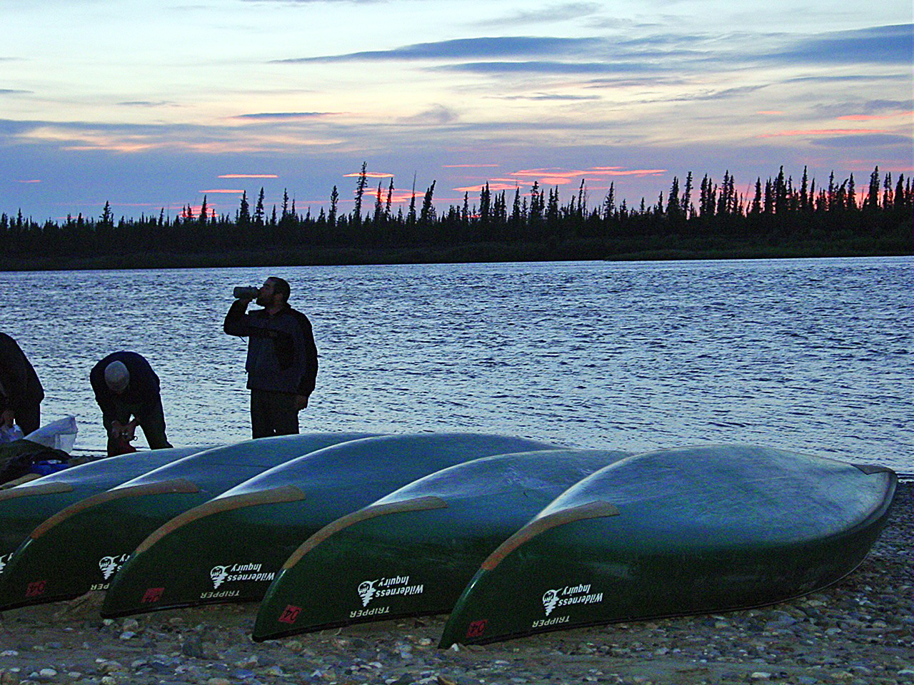 With the midnight sun in the background, a group of people stands and drinks coffee behind a line of tandem canoes on the riverbank.