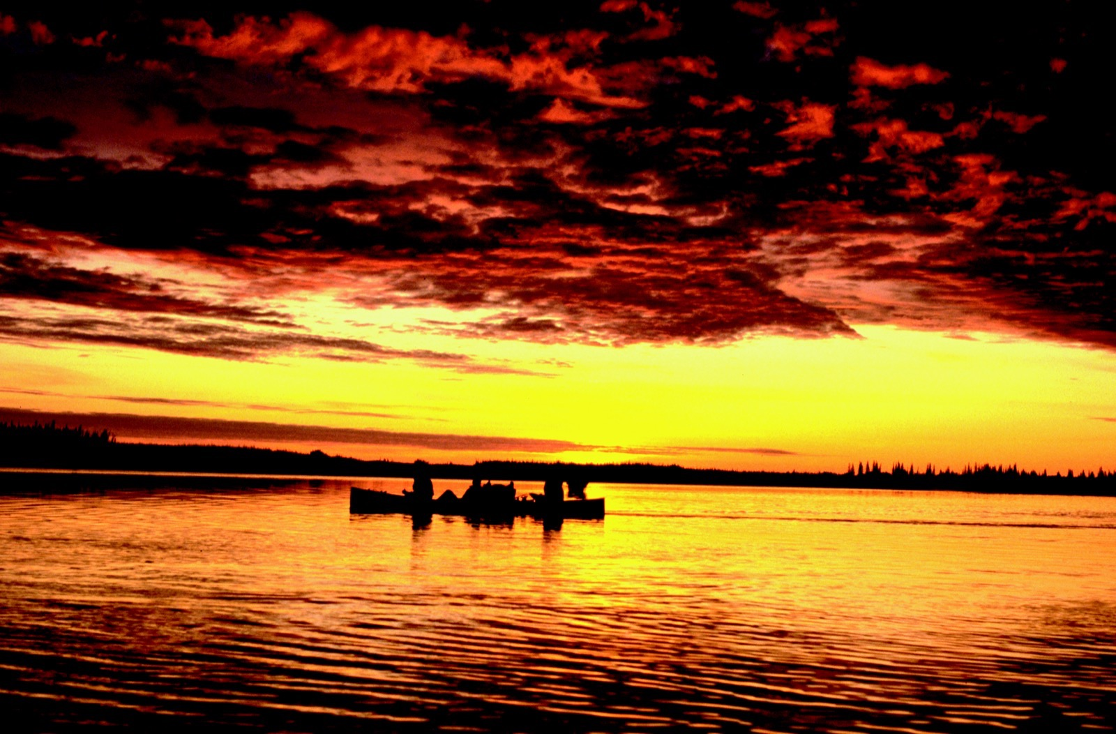 A canoe is backlit by a vibrant red and yellow sky of Alaska's midnight sun.