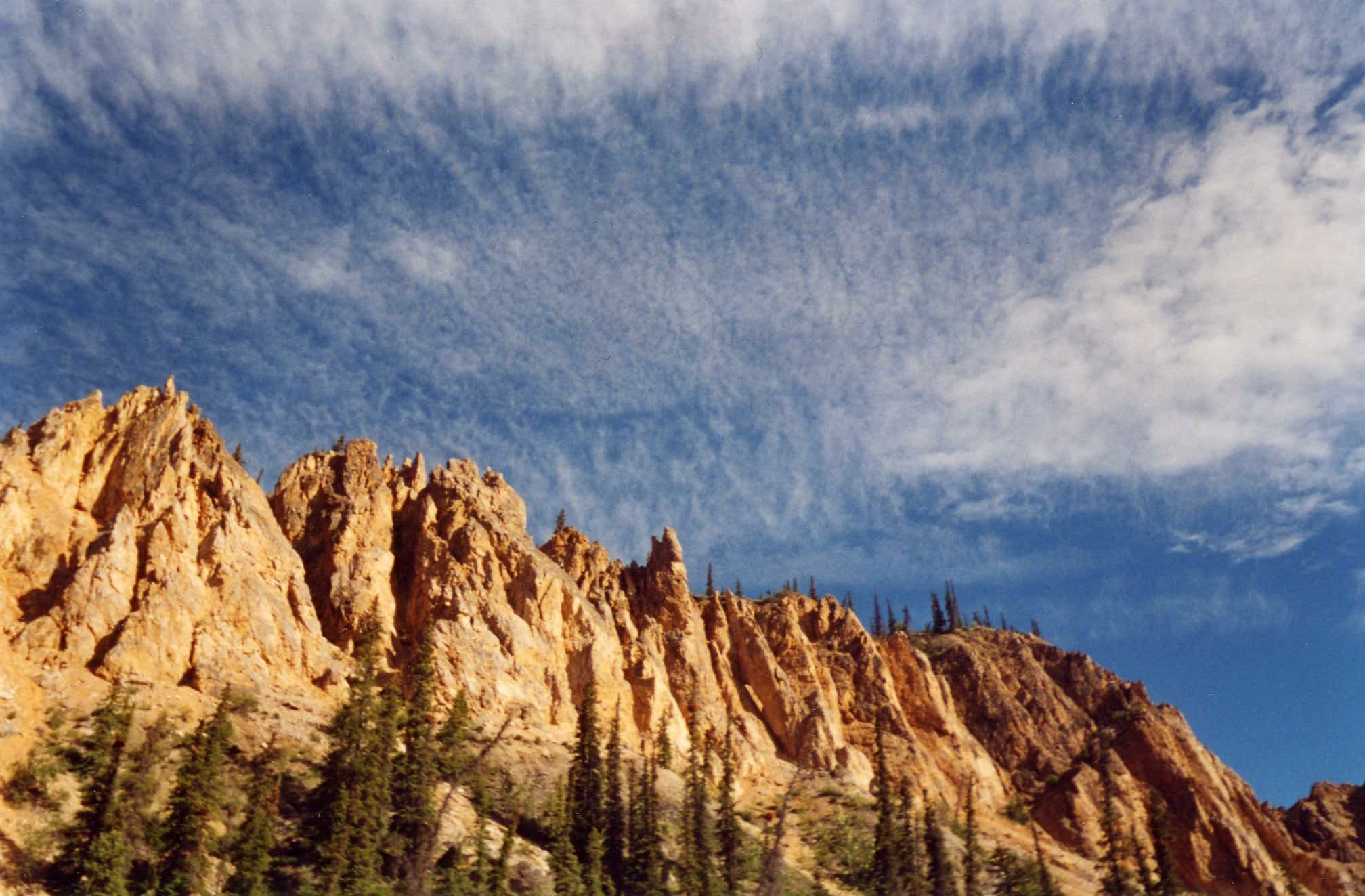 The sandstone formations of Ramparts Canyon pierce the blue sky with wispy clouds.