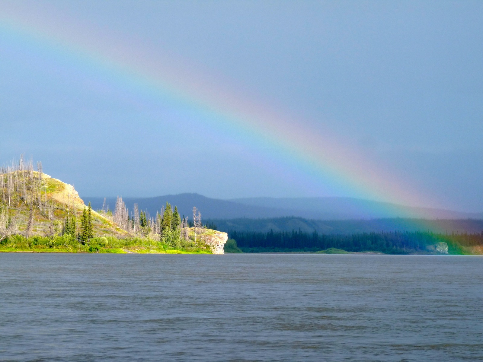 A large rainbow across the sky above the steel-grey water of the Porcupine River.