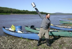 """A man swings a coffee pot to make """"cowboy coffee"""" on the shores of the Porcupine River."""
