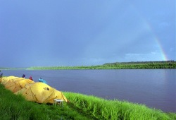 A rainbow over a campsite with North Face dome tents on the grassy banks of Alaska's Porcupine River.