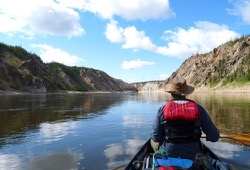 In the foreground, the bow paddler sits in the canoe with paddle in hand, looking out over the steep-banked river ahead.