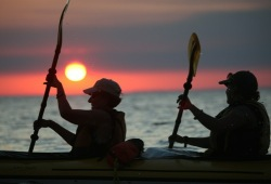 Two kayak paddlers at dusk with setting sun on Lake Superior.