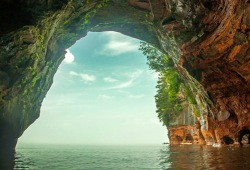 Looking through a large arch of a sea cave.