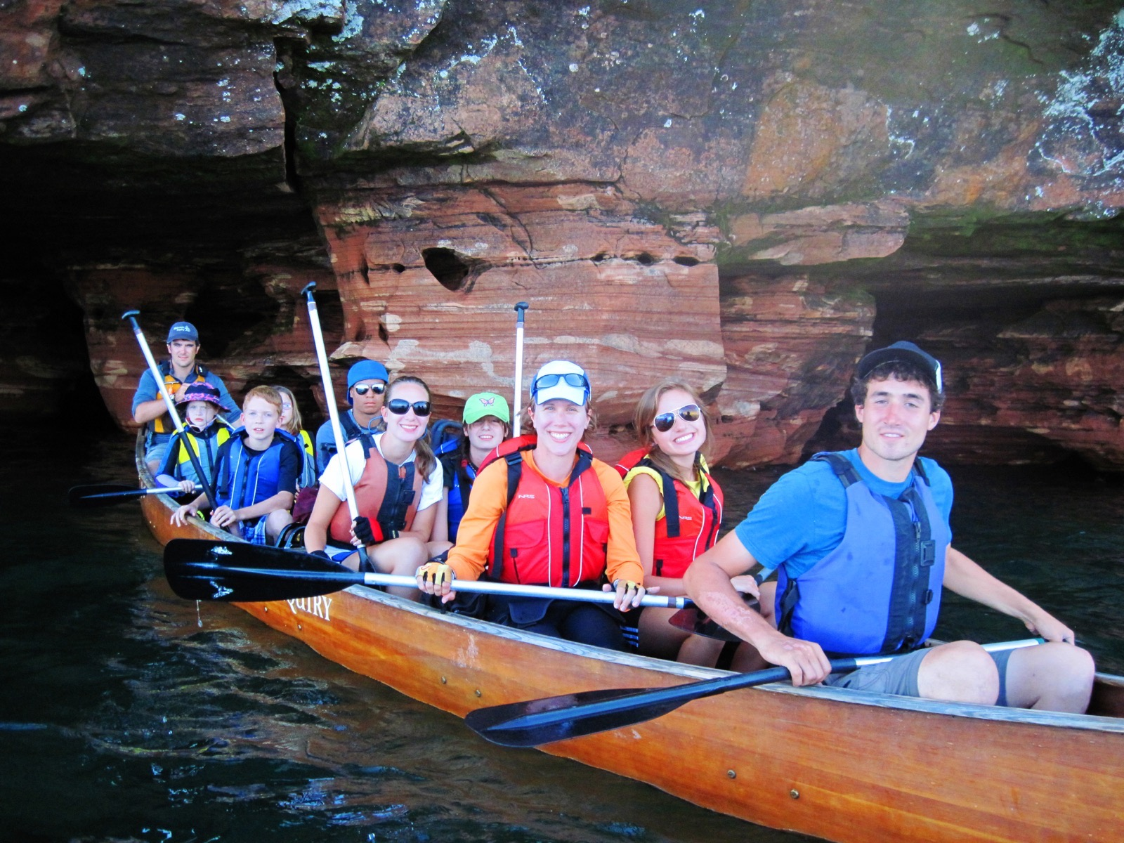 A group of people in a 24-foot Voyageur canoe in front of sea caves.