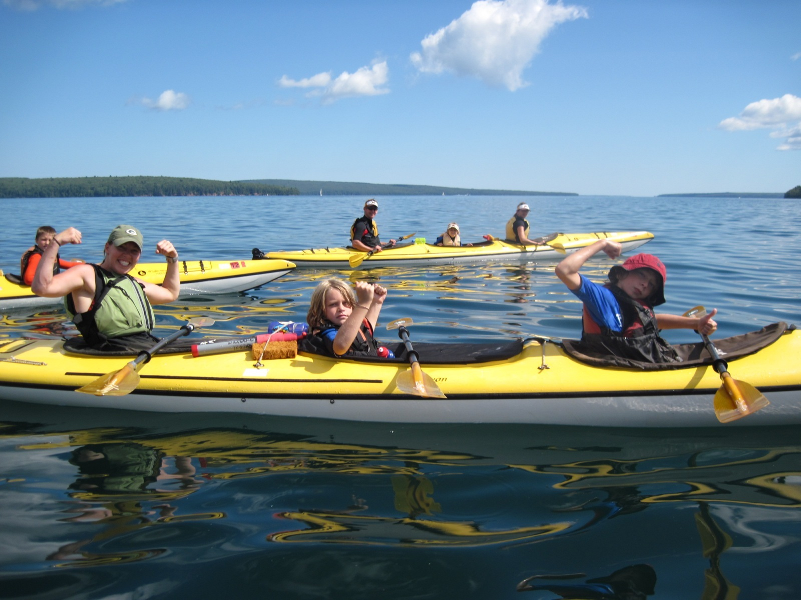 Kids and trip leaders show off their muscles from kayaking while taking a break on their way back to Little Sand Bay.