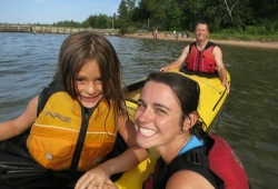 A Wilderness Inquiry guide smiles next to a young girl sitting in a kayak.