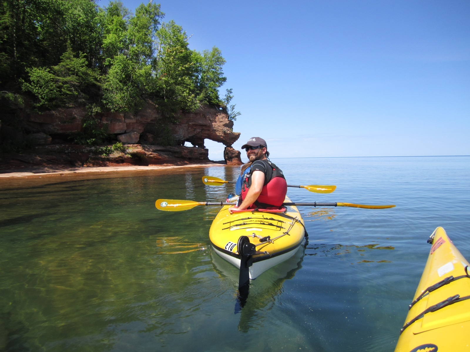 Kayakers stop to examine part of the Apostle Islands shoreline, which forms a hole-in-the-wall rock