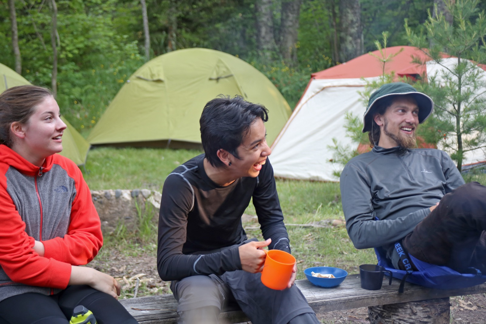 Three young people sitting on a bench at a campsite with tents in the background.