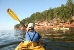 Patti paddles in the bow of a kayak on the way to Mawikwe Bay.