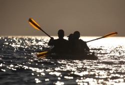 Silhouetted participants in kayak paddle during sunset on Lake Superior.
