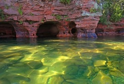 Shallow, green water with red sandstone sea caves in the background.