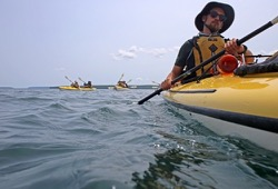 close up photo of a participant paddling a kayak in Lake Superior