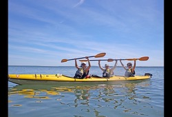 Three people holding paddles in the air while sitting in a yellow kayak.