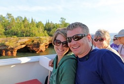 Couple poses for camera on deck of Apostle Islands sunset cruise boat with red cliffs and trees in background.
