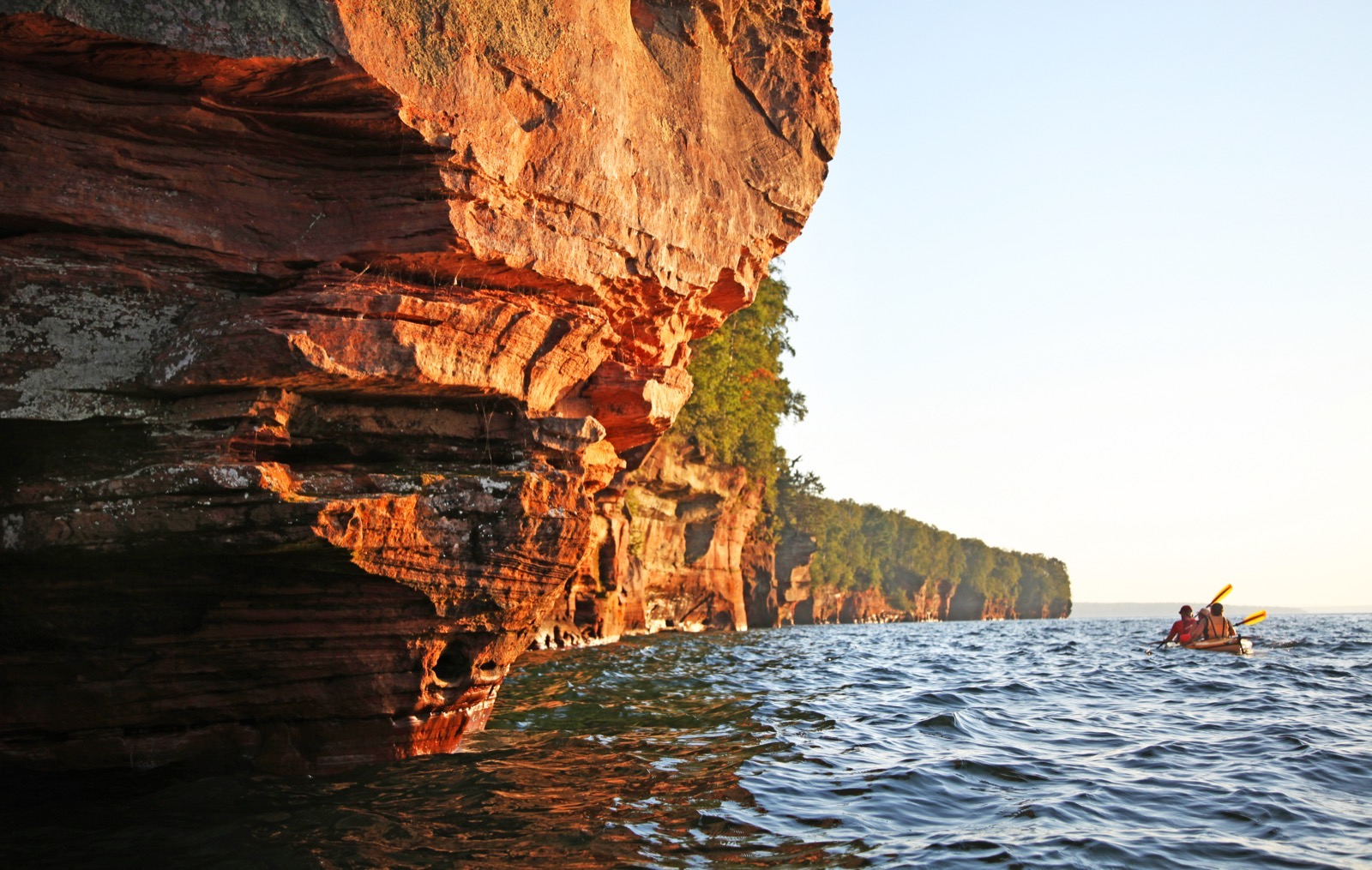 Red sandstone cliffs jutting out over the lake are lit up by the sunset as kayakers paddle away in the distance.