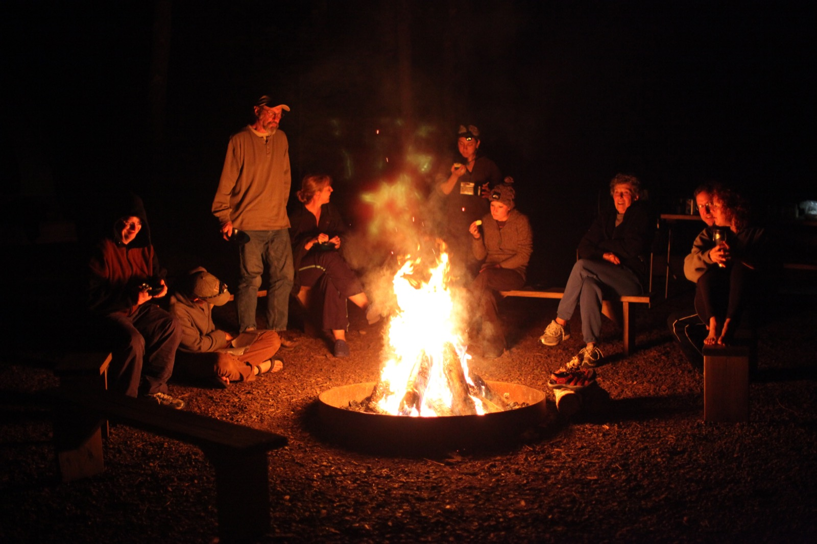 Participants gather around a campfire.