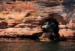 Three people paddle in  yellow sea kayak away from large, red sea cave on an Apostle Islands camping trip.
