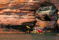 Three people in yellow sea kayak paddle away from arch in large, red sea kayak.