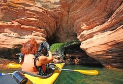 Participant in yellow sea kayak takes picture of arch in red, sea cave.