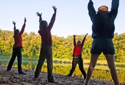 Four people enjoy morning yoga on the beach along the St. Croix River