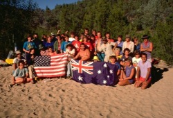 The Wilderness Inquiry group poses with Australians and hold an American flag and an Australian flag on the banks of the Snowy River.