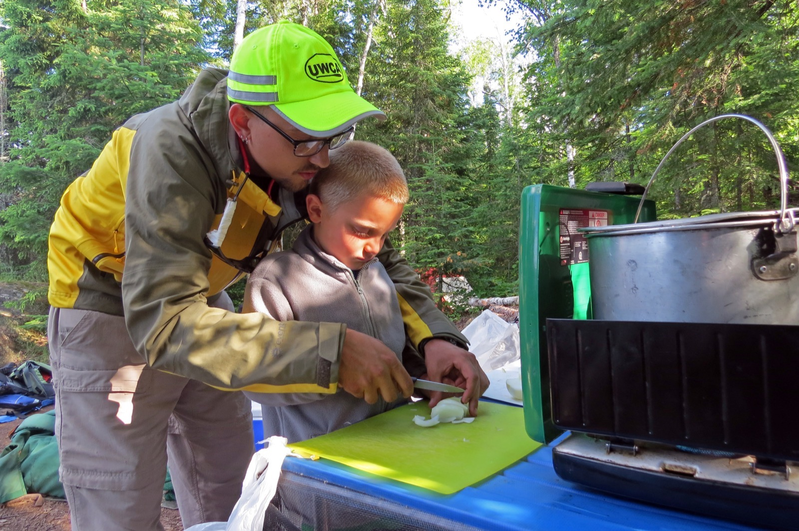 A guide teaches a kid how to chop an onion for dinner at a campsite.