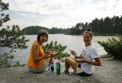 Mother and daughter sitting on a rock by the lake enjoying a meal