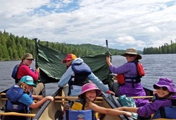 three participants try to make a sail with paddles and a tarp for their canoe on a windy day on the lake