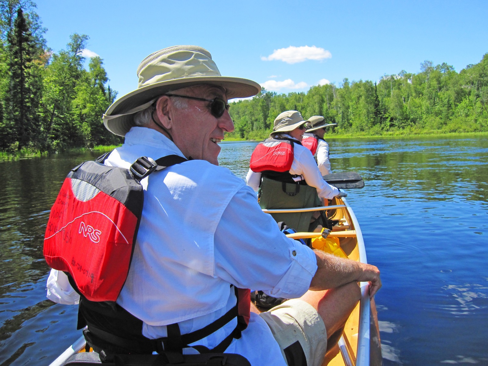 Three people paddle a kevlar canoe in the Boundary Waters on a sunny day.