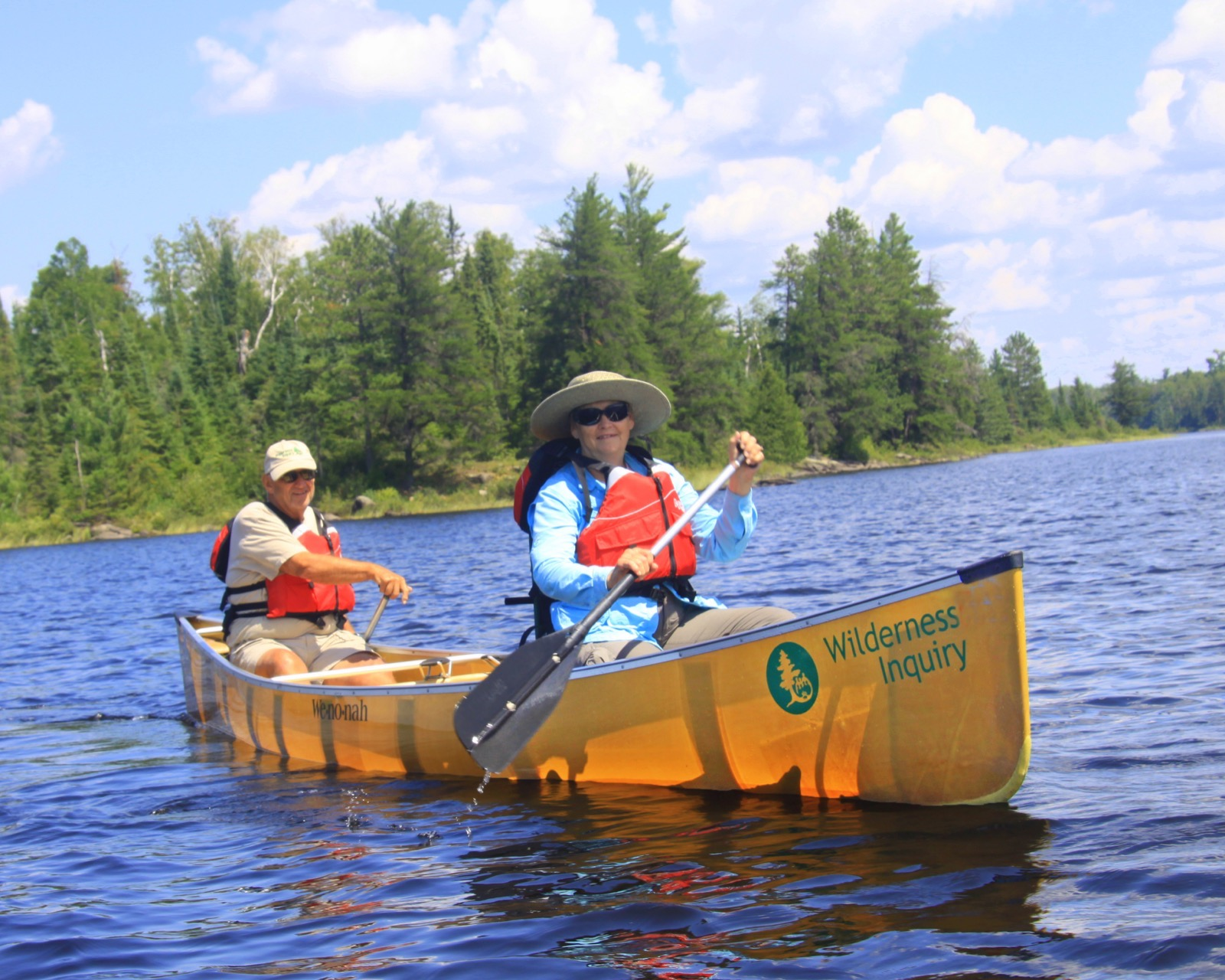 Two people paddle a kevlar canoe on lake near Ely, MN.