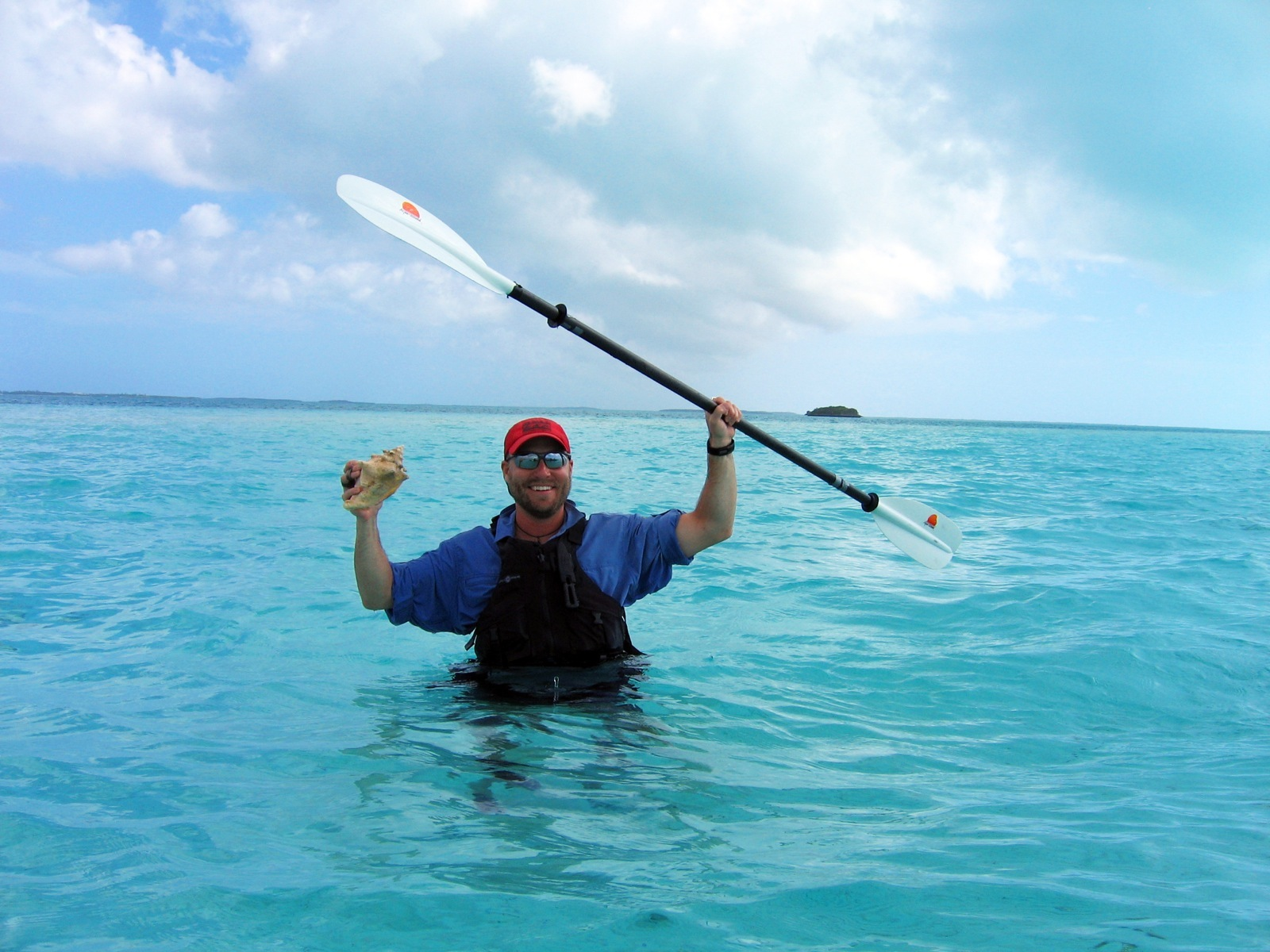 Dave excitedly holds up his kayak paddle and a conch shell as he stands waist deep in the blue waters of the Caribbean.