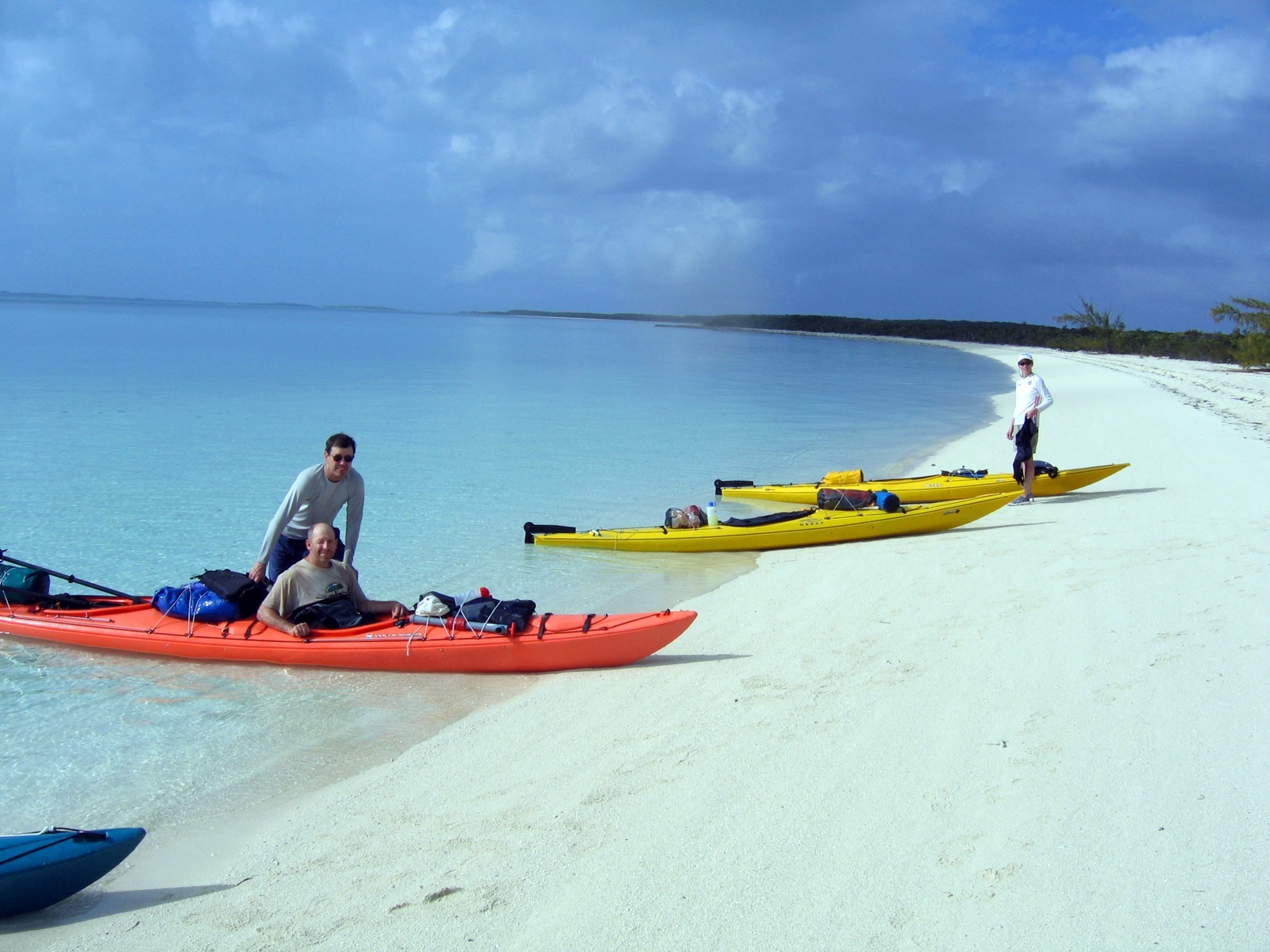 Three men pose with their sea kayaks that are pulled up on the white sands of Norman's Caye as rainclouds start to roll in.