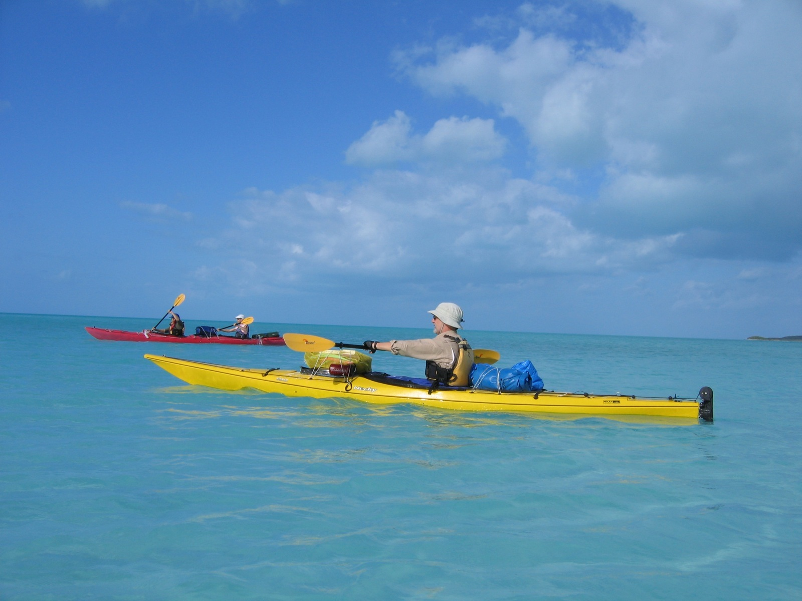 Three Paddlers In Two Sea Kayaks Paddle The Tranquil Blue Waters Of Bahamas Under A
