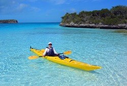 A woman poses for the camera as she sits in a bright yellow sea kayak in striking aquamarine waters near an island.