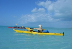 Three paddlers in two sea kayaks paddle the tranquil blue waters of the Bahamas under a bright blue sky.