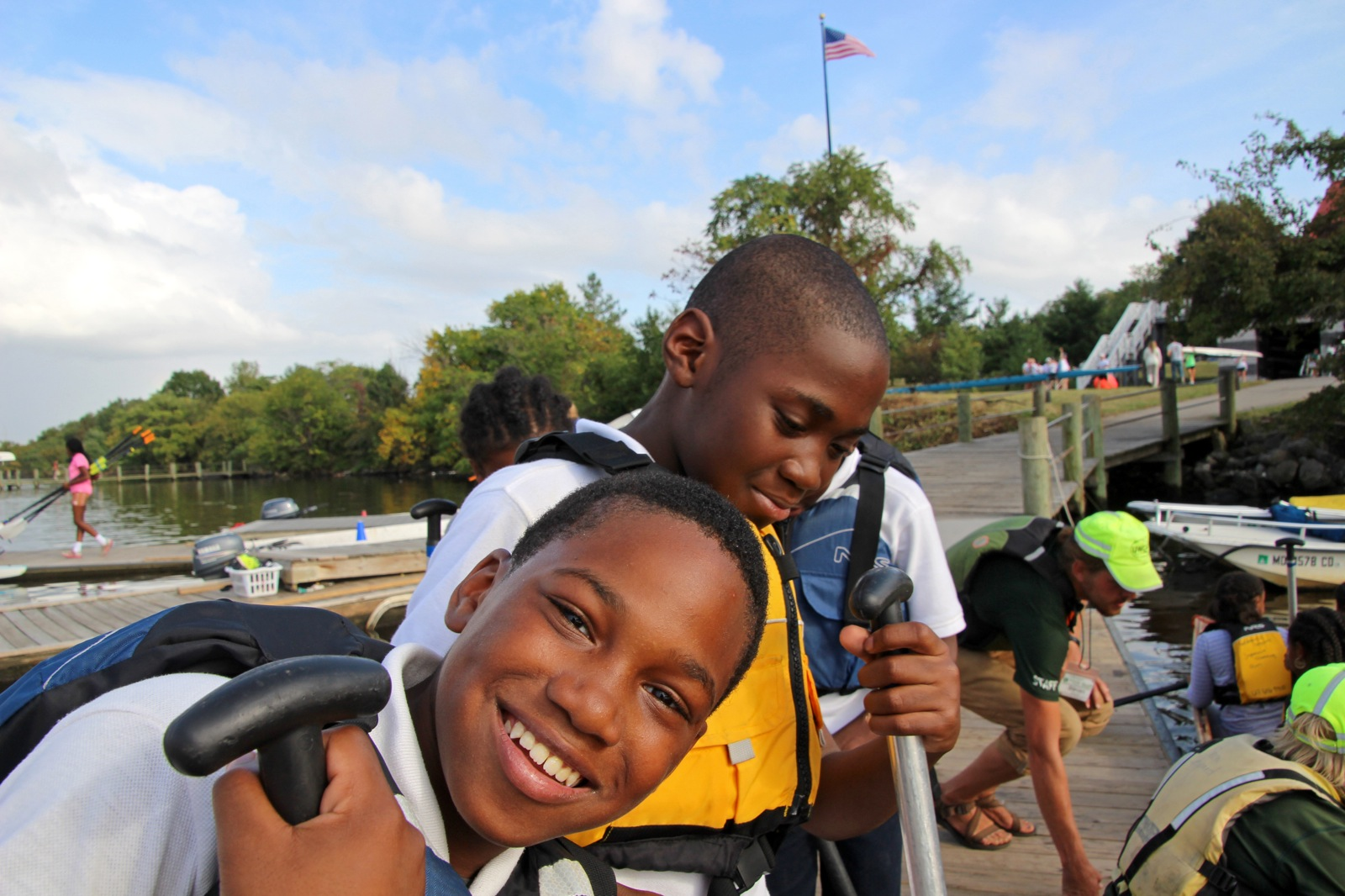 two boys stand on the dock with their life jackets and paddles ready to canoe the Patapsco