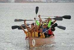 a group of youth and staff raise their paddles above their heads as they celebrate a successful canoe on the lake  in Baltimore