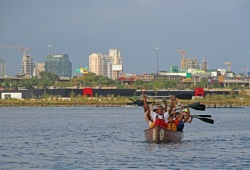 students hold their paddles above their heads in their canoe with the skyline of Baltimore in the back