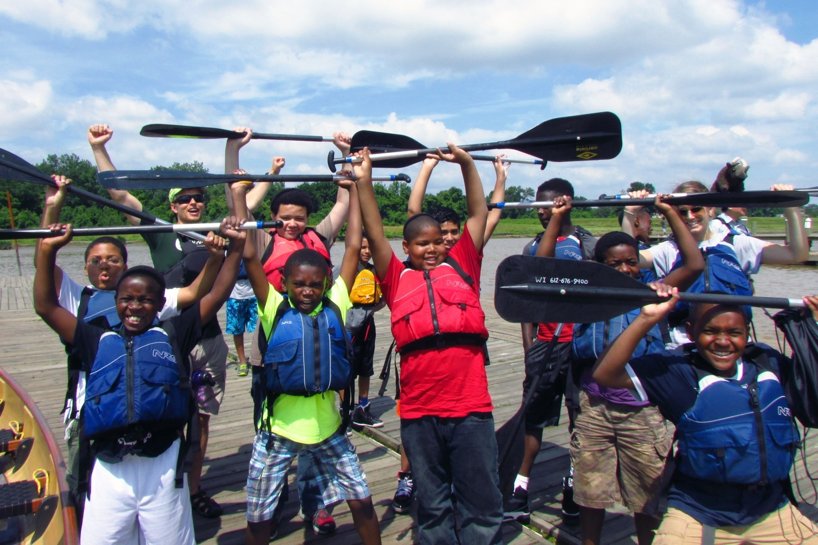 Group of students hold their paddles above their heads after a great canoe