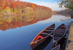 Two Voyageur canoes rest next to shore on a calm river; colorful trees on opposite shore.
