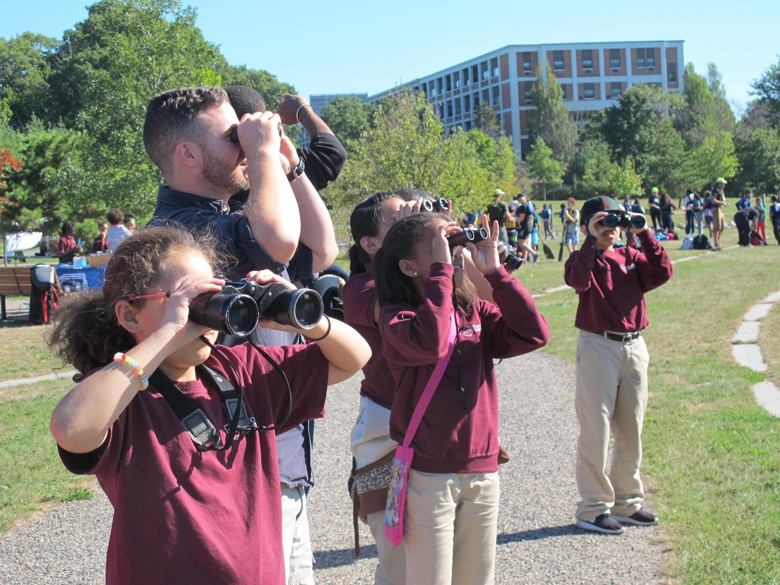 a group of participants look for birds in Boston using their binoculars