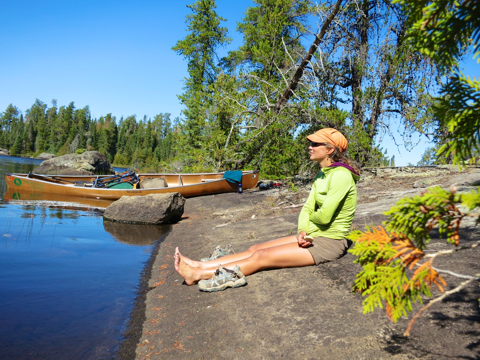 A woman sits on the shore after a day of canoeing